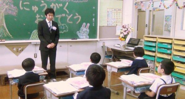 教室で先生の話を聞く新入生の子供たち